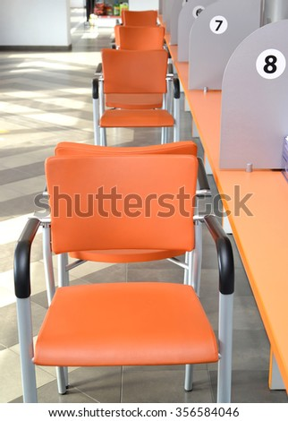 Orange chairs about a collective desktop. Hall of customer service