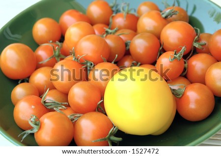 Orange cherry tomatoes and one yellow tomato in a green bowl