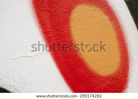 Orange circle inside red circle on the white wall background. - stock photo