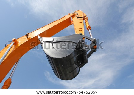 Orange clear excavator bucket against the blue sky - stock photo