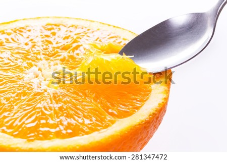 Orange close up. Eating an orange with spoon. Macro shot. Healthy lifestyle.  - stock photo