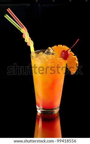 orange cocktail with a cherry on black with reflection