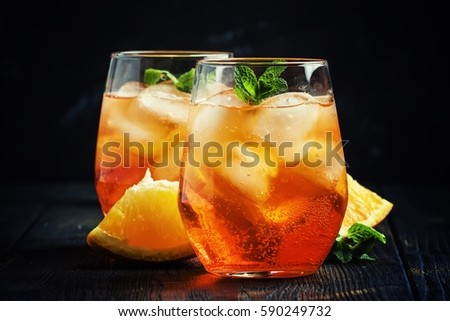 Orange cocktail with ice, black background, selective focus