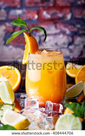 Orange cocktail with ice cubes in the tropical bar at brick wall background - stock photo