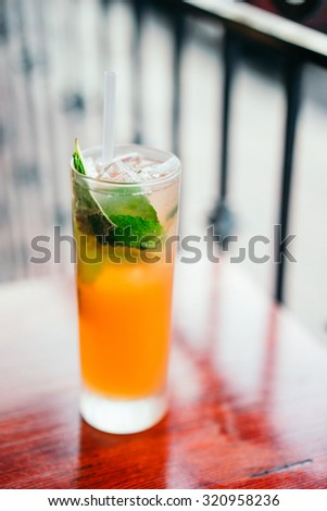 Orange cocktail with mint leaves outdoors
