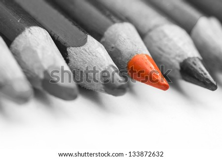 Orange Coloring Crayon Standing Out From Larger Group Of Coloring Crayons - stock photo