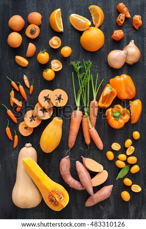 orange coloured fruit and vegetables on dark rustic distressed background, part of a collection