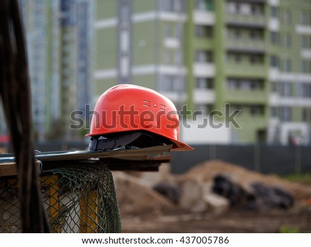 Orange construction helmet lies on a metal structure against a background of construction of fences and buildings - buildings. A piece of wire mesh. Construction site - stock photo