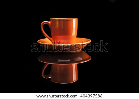 Orange cup isolated on black background with reflexion - stock photo
