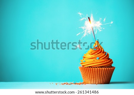 Orange cupcake with sparkler and copy space to side - stock photo