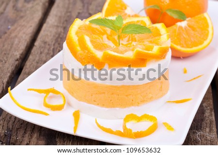 orange dessert with fresh fruits on a white plate on wooden board - stock photo