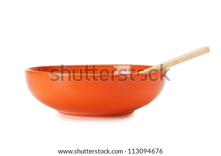 orange empty ceramic bowl and wooden spoon  isolated on white background