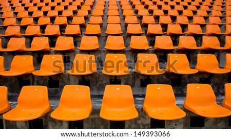 Orange empty stadium seats in arena  - stock photo