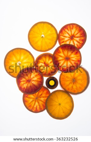 Orange essential oil bottle with orange slices (top view)