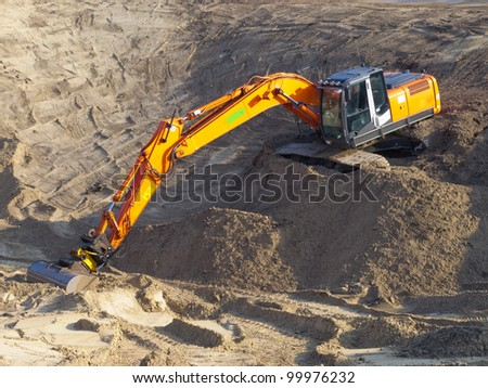 Orange excavator at work in a large sandpit - stock photo