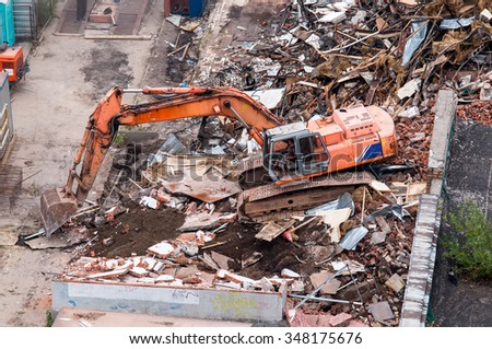 Orange excavator destroys a house, Moscow, Russia - stock photo