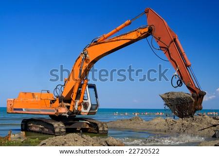 Orange Excavator on the beach - stock photo
