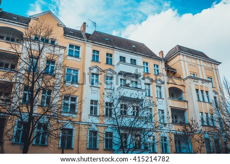 orange facade with blue sky of apartment house - stock photo