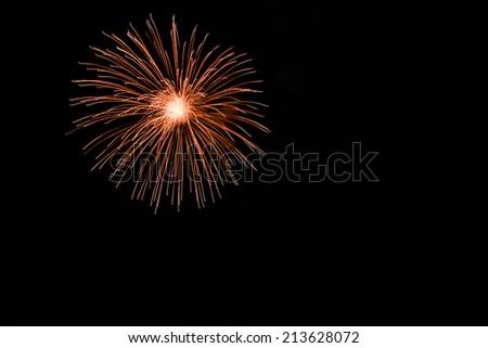 Orange fireworks on the black sky background - stock photo