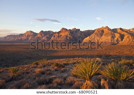 Orange first rays of dawn light on the cliffs of Nevada's Red Rock National Conservation Area. - stock photo