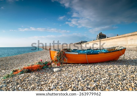 Orange fishing boat on Chesil Beach at Portland near Weymouth on the Jurassic Coast of Dorset - stock photo