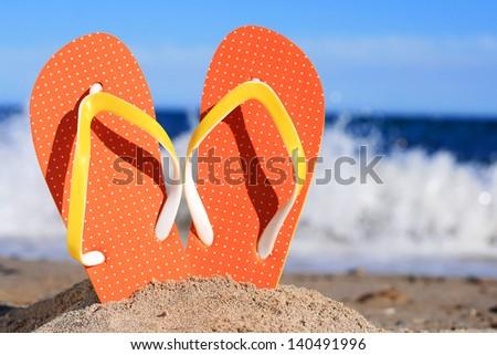 Orange flip-flops in sand on the beach in Barcelona. - stock photo
