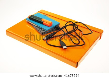 orange folder, external hard disk and marker