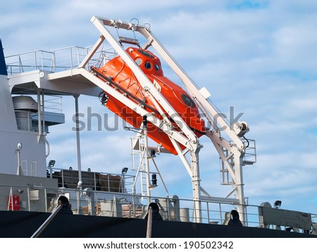 orange free-fall life boat for emergency evacuation - stock photo