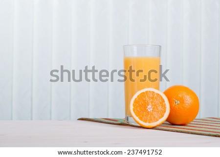 Orange fresh juice beside delicious ripe oranges on the table - stock photo
