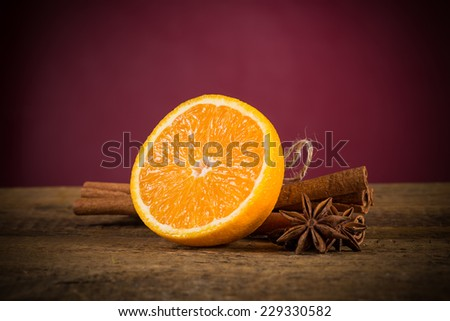 Orange fruit, cinnamon sticks and anise stars on wooden table - stock photo