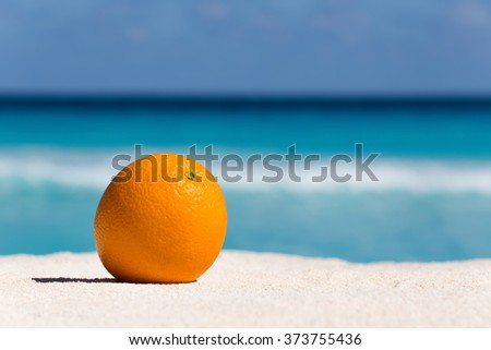 Orange fruit on sand against turquoise caribbean sea water. Tropical summer vacation concept - stock photo