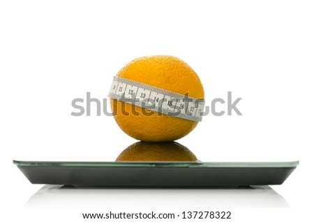 Orange fruit wrapped with measuring tape on a scale. Concept of dieting. Isolated over white background. - stock photo