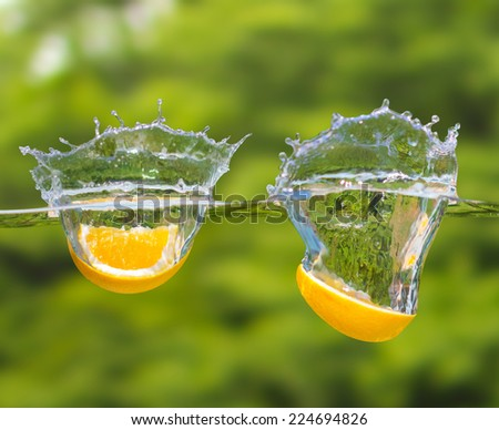 Orange fruits fall deeply under water with a big splash on green nature background - stock photo