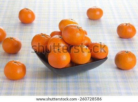 Orange fruits in a bowl on a picnic table - stock photo