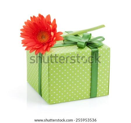 Orange gerbera flower over gift box. Isolated on white background - stock photo