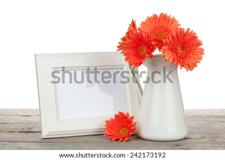 Orange gerbera flowers and photo frame on wooden table on white background - stock photo