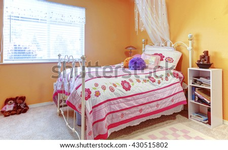 Orange girl teenager kids bedroom with toys, white bed frame. - stock photo