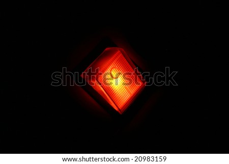 Orange glowing power button on a black pattern background - stock photo
