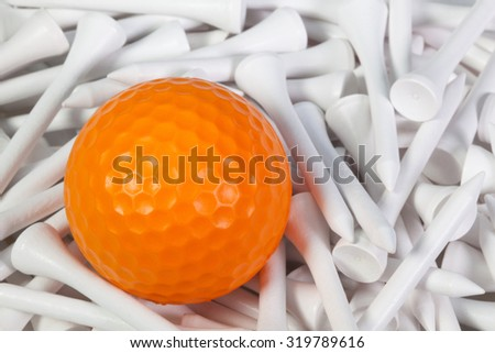 Orange golf ball lying between white wooden golf tees - stock photo