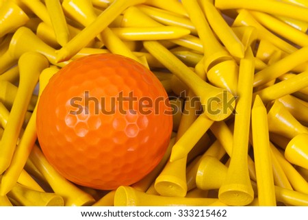 Orange  golf ball lying between yellow wooden golf tees - stock photo
