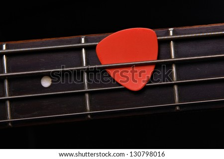 Orange guitar pick on the fingerboard - stock photo