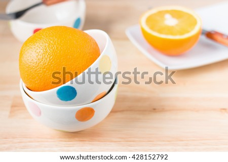 Orange, half of orange in ceramic cups, plates and cutlery on wooden table.