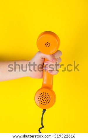 Orange handset in hand on a yellow background