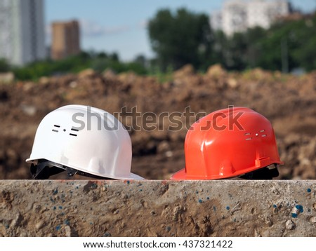 Orange helmet builder and a white helmet engineer. Helmets lie on a concrete block on the background of the wasteland. In the distance, the city houses. Future construction planning. - stock photo