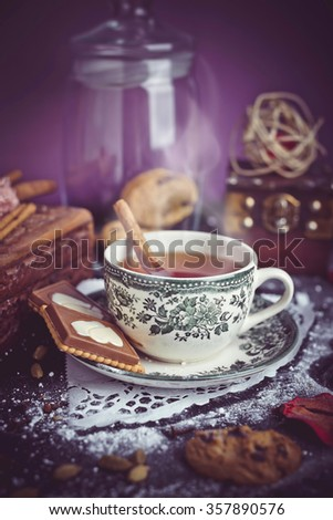 Orange herbal tea with cinnamon and chocolate cake in beautiful retro vintage cup. Decoration with cookies, cardamom and clove/Orange herbal tea with cinnamon stick - stock photo