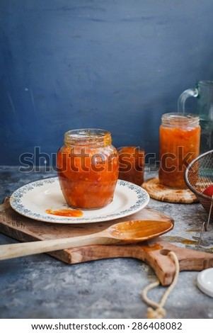 Orange homemade marmalade in jars over on rustic cutting board. Rustic image with copy space for your text.  - stock photo