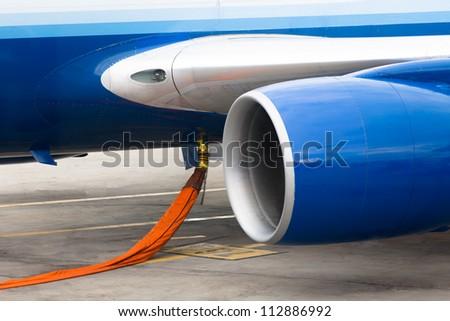 Orange hose ready to refill kerosene gas in to tanks of a jet plane - stock photo
