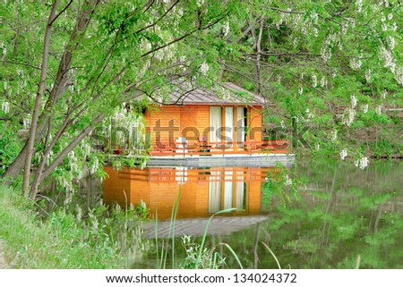 orange house on the calm lake surface into green forest - stock photo