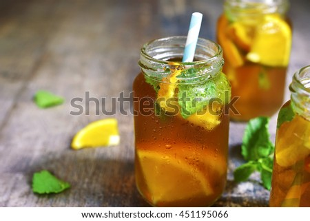 Orange iced tea in a glass jar with paper straws on a rustic wooden background. - stock photo