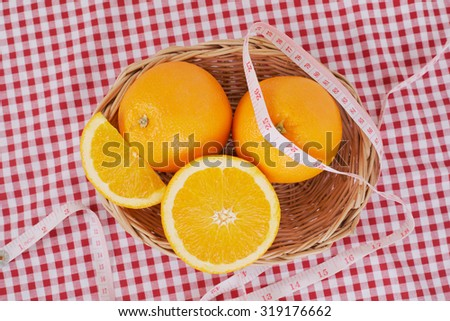orange in basket  and centimeter on table cloth for lose weight  - stock photo